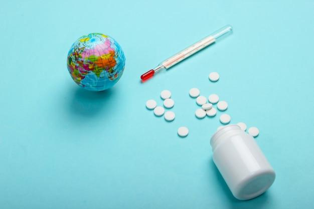 Światowa martwa pandemia. glob, termometr z butelką tabletek na niebieskim tle. epidemia koronowirusa