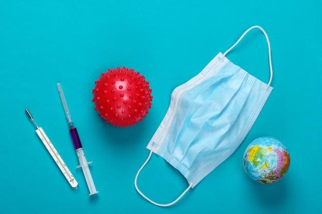 Światowa pandemia. strzykawka, materiały medyczne, szczep wirusa, kula ziemska na niebiesko