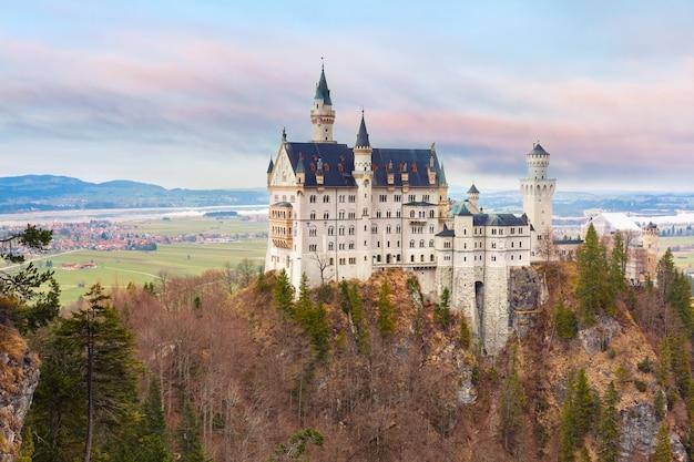 Światowej sławy atrakcja turystyczna w alpach bawarskich, bajkowy neuschwanstein lub nowy zamek swanstone, xix-wieczny pałac odrodzenia romańskiego o zachodzie słońca, hohenschwangau, bawaria, niemcy