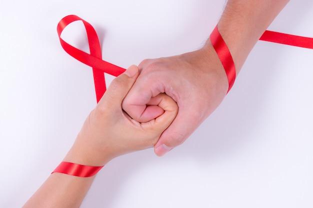 Światowy dzień aids. mężczyzna i kobieta, trzymając się za ręce z czerwoną wstążką. wspomaga świadomość.