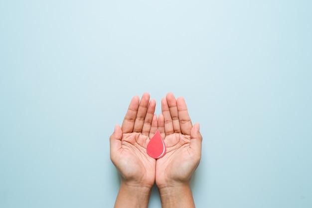Światowy dzień cukrzycy i świadomość niebieskiej wstążki z czerwoną kroplą krwi w rękach kobiety na białym tle na niebieskim tle. światowy dzień cukrzycy, 14 listopada. skopiuj miejsce. widok z góry