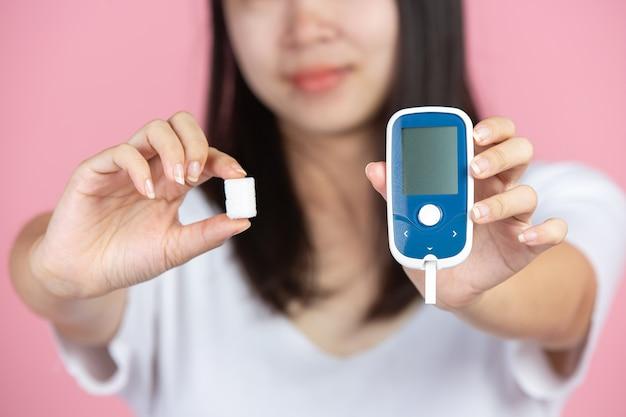 Światowy dzień cukrzycy; kobieta trzyma glukometr i kostki cukru na różowej ścianie