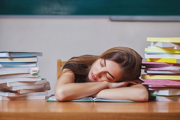 Światowy dzień książki. młoda kobieta zasnęła podczas czytania książek przy stole