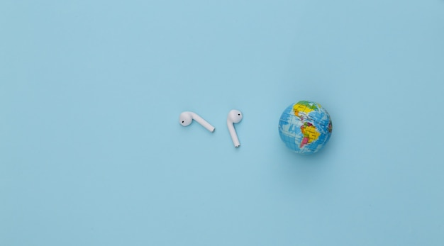 Światowy dzień muzyki. globus i bezprzewodowe słuchawki na niebieskim tle.