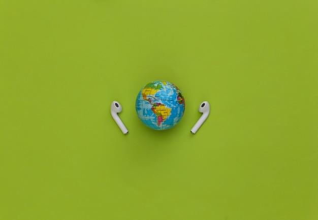 Światowy dzień muzyki. globus i bezprzewodowe słuchawki na zielonym tle.
