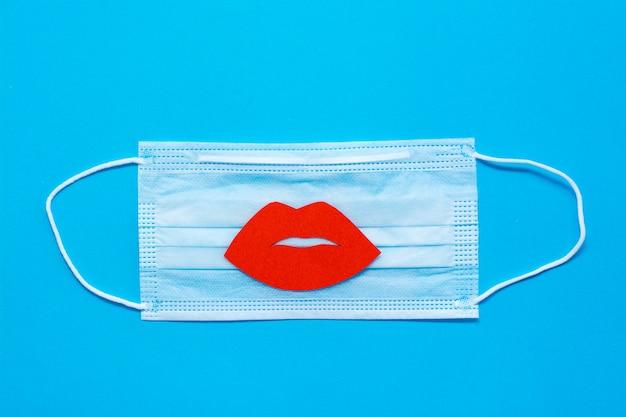 Światowy dzień pocałunku. czerwone usta na ochronnej masce medycznej na niebieskim tle. koronawirus pandemia