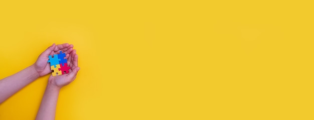 Światowy dzień świadomości autyzmu ręce małego dziecka trzymającego kolorowe puzzle na żółtym tle