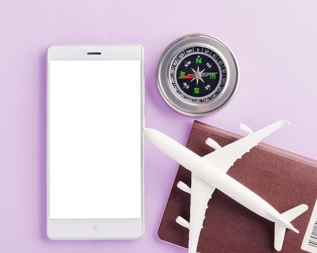 Światowy dzień turystyki minimalna zabawka model kompas samolotu i nowoczesny inteligentny telefon komórkowy pusty ekran