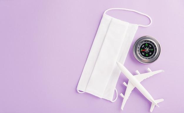 Światowy dzień turystyki minimalna zabawka model samolot kompas i maska ochronna pandemiczna koronawirus