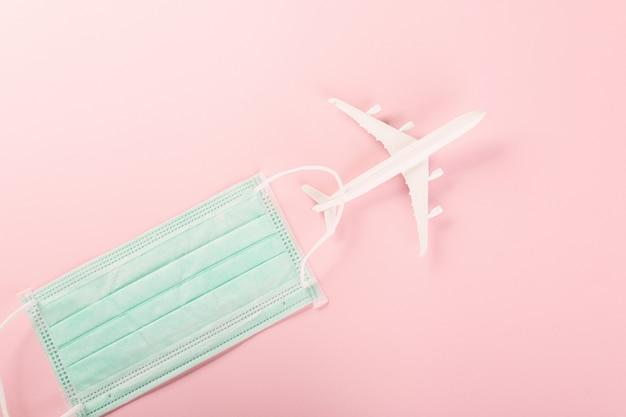 Światowy dzień turystyki widok z góry model samolotu i medyczna maska na twarz akcesoria wakacyjne wycieczka na plażę podróż