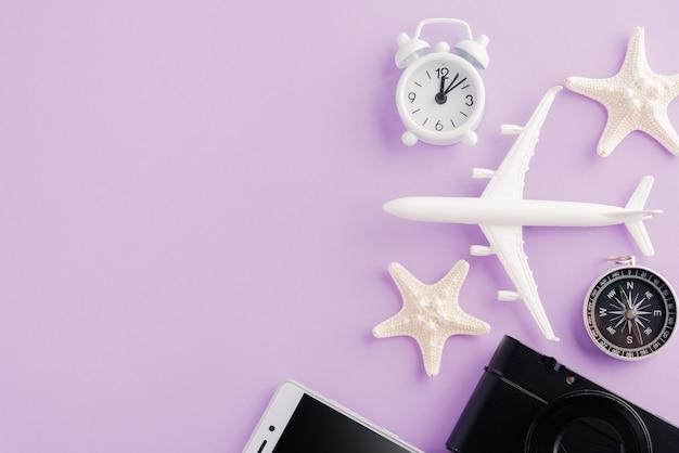 Światowy dzień turystyki widok z góry na minimalny model samolotu rozgwiazda budzik kompas i smartfon