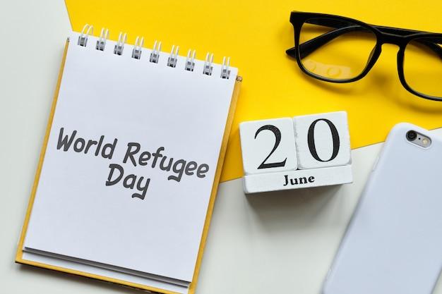 Światowy dzień uchodźcy 20 czerwca kalendarz miesiąca koncepcja na drewniane klocki.
