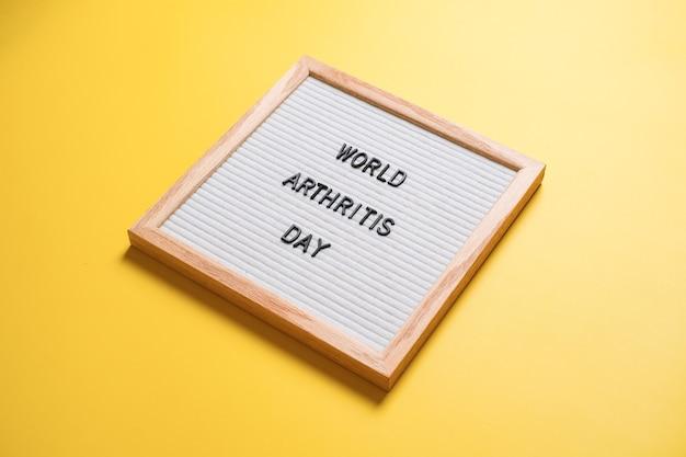 Światowy dzień zapalenia stawów napis z białej tablicy na jasnym żółtym tle.