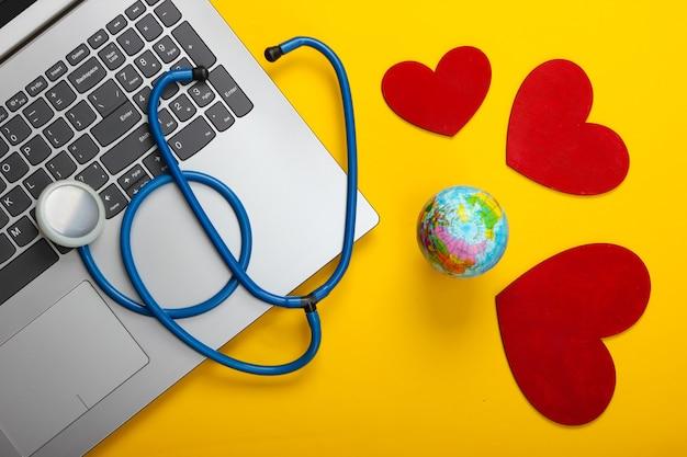 Światowy dzień zdrowia. laptop i stetoskop z sercem, kula ziemska na żółto