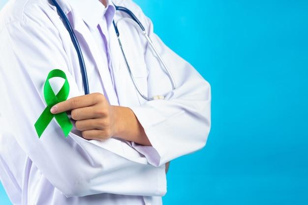 Światowy dzień zdrowia psychicznego. ręka lekarza trzymając zieloną wstążkę