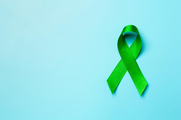 Światowy dzień zdrowia psychicznego. zielona wstążka na niebieskim tle