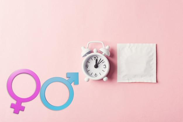 Światowy dzień zdrowia seksualnego lub prezerwatywy i budzik antykoncepcja znaki płci męskiej i żeńskiej