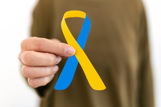Światowy dzień zespołu downa niebieska żółta wstążka świadomości w dłoni dla podniesienia wsparcia