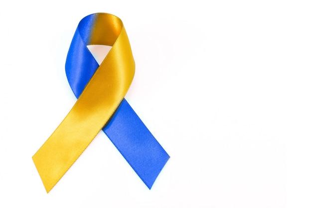Światowy dzień zespołu downa z niebiesko-żółtą kokardą wstążki świadomości.