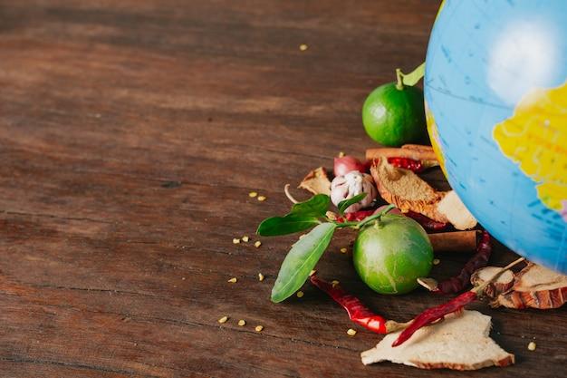 Światowy dzień żywności, zapakowana w samochód przyprawa i świeże kolory umieszczone na symulowanej kuli ziemskiej na brązowej drewnianej podłodze.