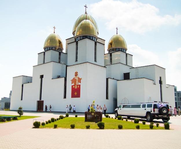 Świątynia, kościół ze złotą kopułą i ślubna limuzyna