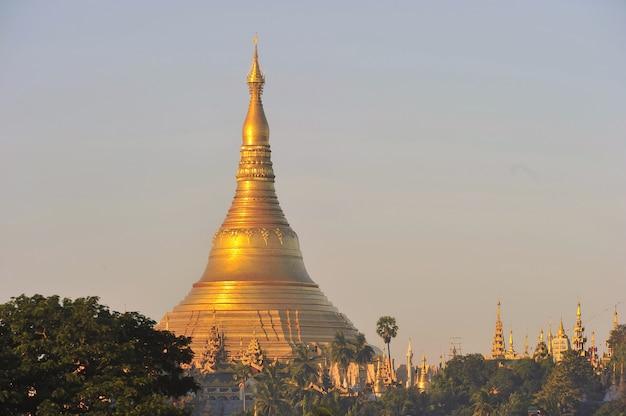 Świątynia pagoda shwedagon z wioską poniżej w porannym świetle w yangon, myanmar (birma)