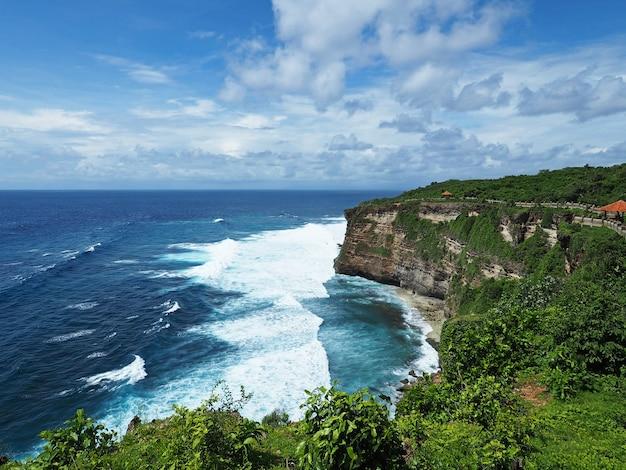 Świątynia uluwatu z widokiem na ocean i klif z jasnego nieba na bali, indonezja.