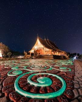 Świątynia wat sirindhorn wararam lub wat phu prao z oświetlonym kościołem i świecącą rzeźbą w nocy w ubon ratchathani