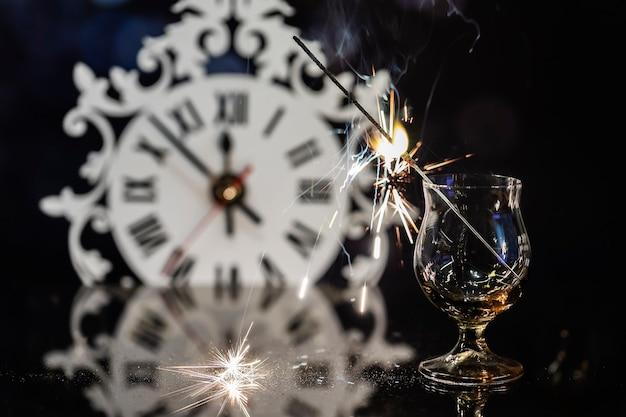Świeca bengalska w szklance na tle zegara.