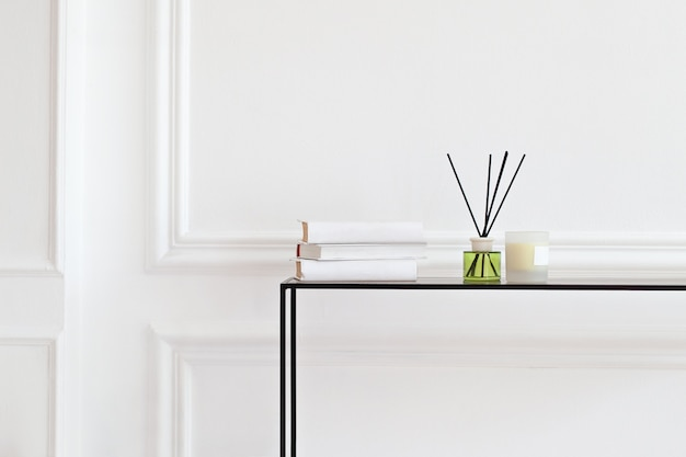 Świeca i aromatyczny odświeżacz trzcinowy na stole w salonie spa. aromatyczny płyn w szklanej butelce z trzcinami. zapach dyfuzor luksusowy w sypialni. hygge. skandynawskie świece do dekoracji wnętrz, zapach, książki