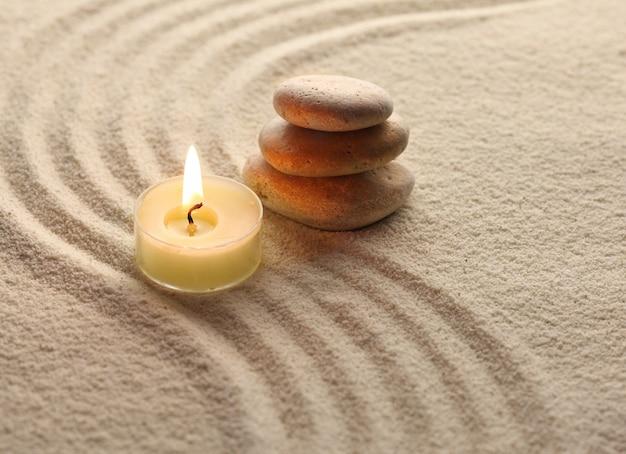 Świeca i kamienie na piasku
