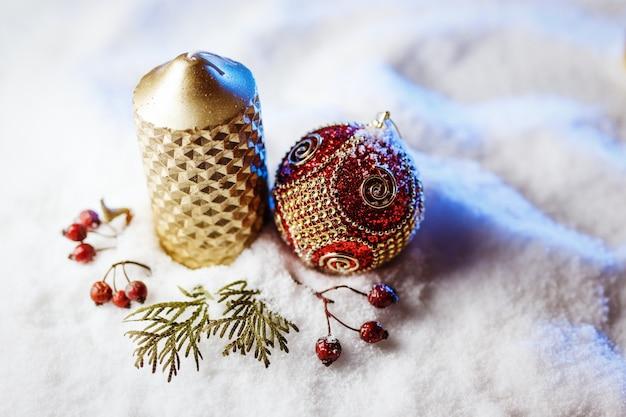 Świeca i świąteczna dekoracja w śniegu z niebieskim światłem.