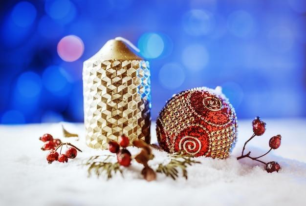 Świeca i świąteczne dekoracje w śniegu z niebieskim tle światła.