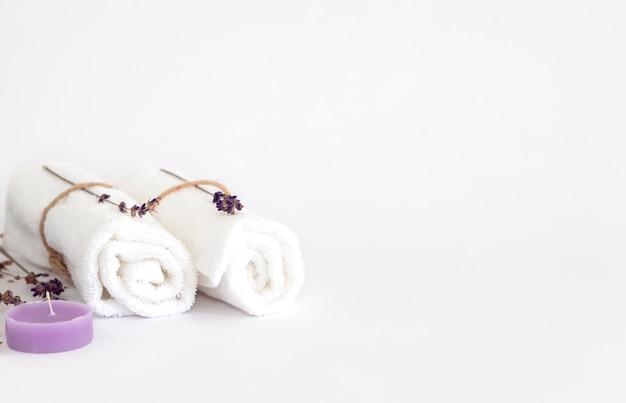 Świeca lawendowa, białe ręczniki i gałązki lawendy
