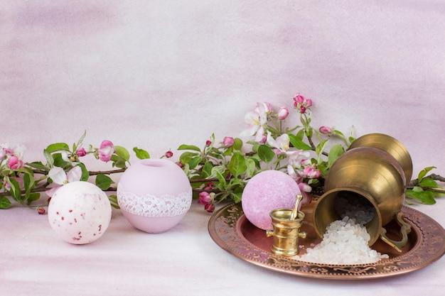 Świeca, mydło, sól do kąpieli w starym złotym dzbanku i gałęzie jabłoni