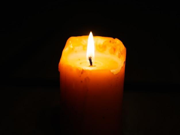 Świeca na ciemnej ścianie. płonąca świeca podczas festiwalu światła. świeca w ciemnej ścianie.