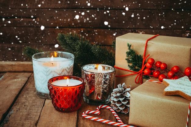 Świeca świąteczna nocą w wesołych świąt i święta nowego roku z rustykalnym ręcznie robionym prezentem, pudełkami prezentowymi. odcień rocznika.