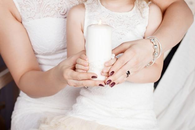 Świeca świąteczna. ręki matki i córki mienia płonąca świeczka.