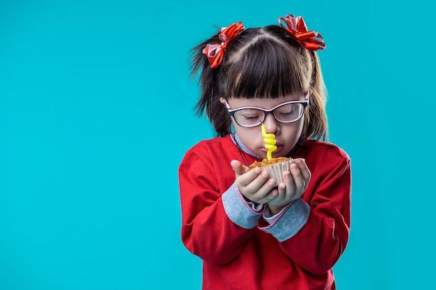 Świeca ułożona w środku. ładna dziewczynka ubrana w czerwoną bluzę z kapturem, trzymająca muffinkę i wąchająca ją