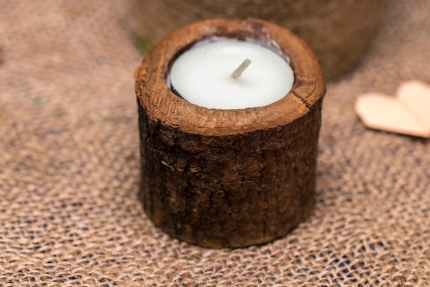 Świeca w drewnianym świeczniku na romantycznym tle.