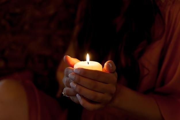 Świeca w kobiecych rękach na czarno