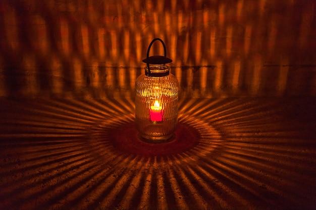 Świeca w szklanych świecznikach odzwierciedla piękny rysunek