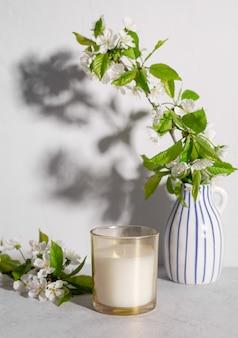 Świeca zapachowa i kwiaty wiśni w wazonie przytulna wiosenna martwa scena