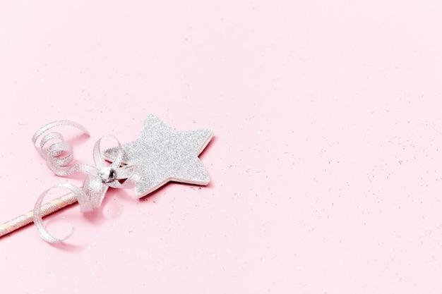 Świecąca, błyszcząca gwiazda na różowym tle z miejsca na kopię. magiczna gwiazda, spełnienie życzeń, marzeń.