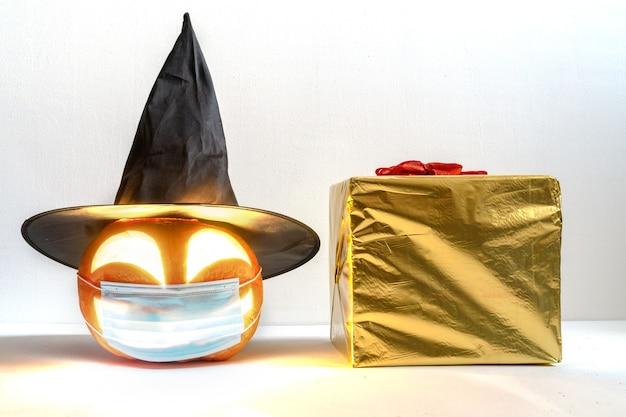 Świecąca dynia halloweenowa w ochronnej masce medycznej