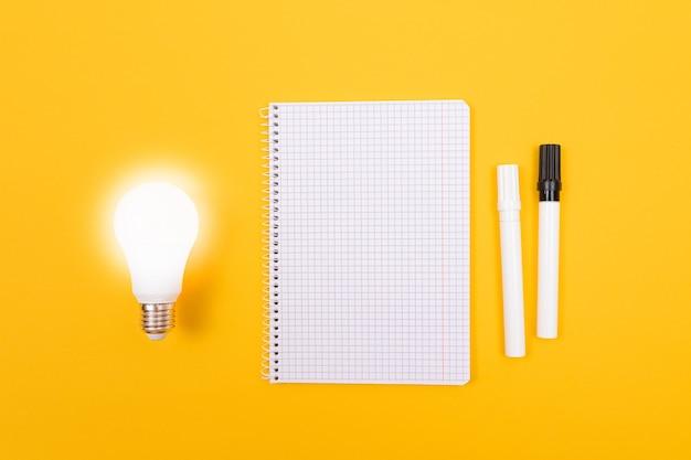 Świecąca lampa energooszczędna z notatnikiem leżącym na żółtym stole