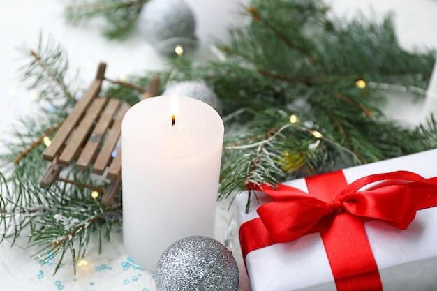 Świecąca świeca z dekoracją świąteczną i prezentem na białej powierzchni