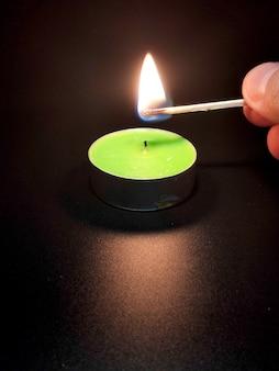 Świecąca zielona świeczka na czarnym stole