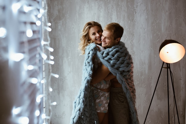 Świecące girlandy noworoczne. stylowe wnętrze. para przy oknie, pod niebieskim kocem dużego krycia. łagodny uścisk i pocałunki. historia miłosna.