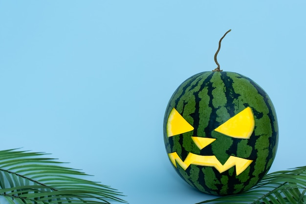 Świecące rzeźbione halloween arbuza na niebieskim tle z liśćmi palmowymi. zielona latarnia o jack z miejsca na kopię.